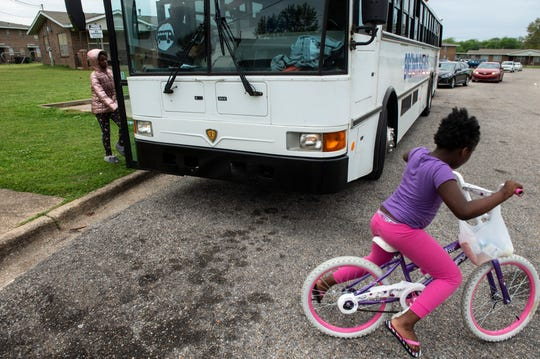 YMCA hands out meals on the Brown Bag Bus in the Gibbs Village neighborhood in Montgomery, Ala., on Monday, March 23, 2020.