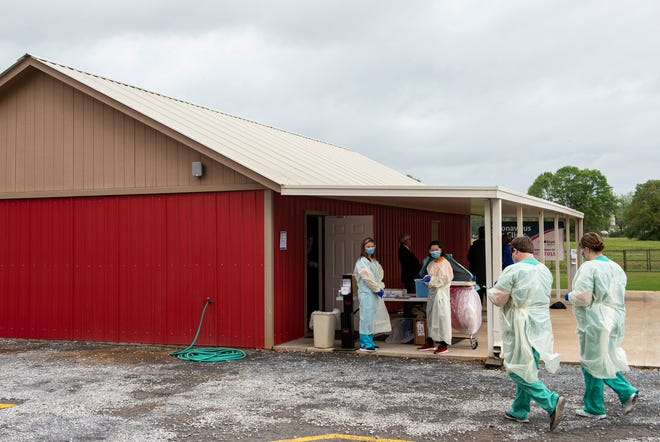 Healthworkers prepare for patients at the Baptist Health coronavirus testing clinic in Prattville, Ala., on Monday, March 23, 2020.