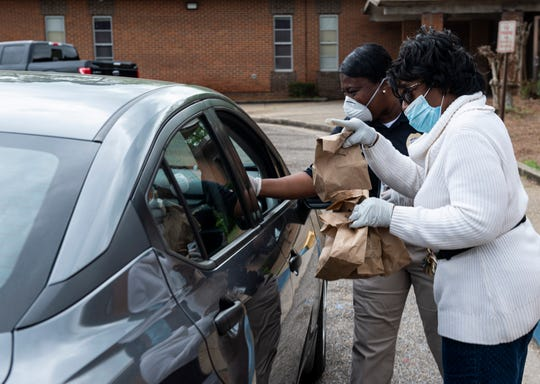 Officer Nicole Huffman and volunteer Lois Coleman hand out meals during lunchtime at Crump Elementary School in Montgomery, Ala., on Monday, March 23, 2020.