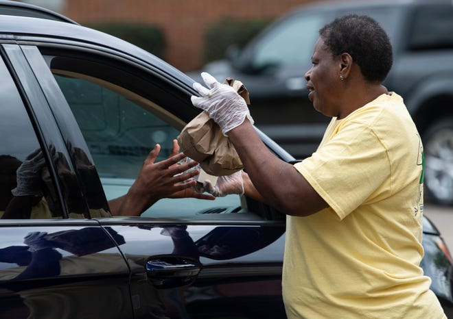 Lunch room manager Diana Caldwell hands out meals during lunchtime at Crump Elementary School in Montgomery, Ala., on Monday, March 23, 2020.