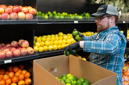 Produce manager John Nolan restocks limes at The Turnip Truck Monday, March 23, 2020, in Nashville, Tenn.