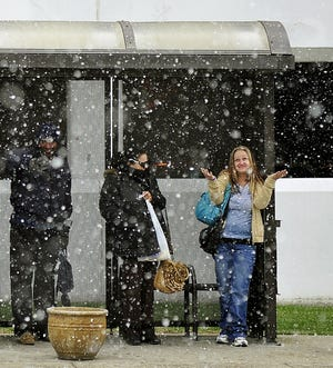 Richard Harris, left, Najwl Ayad, and Sharon Mendoza wait in the snow for a bus at a bus stop across General Hospital in Nashville March 25, 2014.