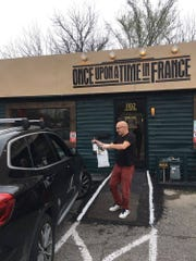 Chef Laurent Champonnois of East Nashville's Once Upon a Time in France delivers food and a bottle of wine in the parking lot to a to-go customer.