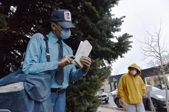 A man wearing a mask walks past the statue of a postal worker wearing a mask at the Post Office in downtown Ridgewood, N.J. on Monday March 23, 2020.