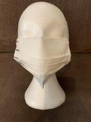 A surgical-style face mask made from a vacuum bag by Rita Petry of Stillwater, New Jersey is fitted on a foam head.
