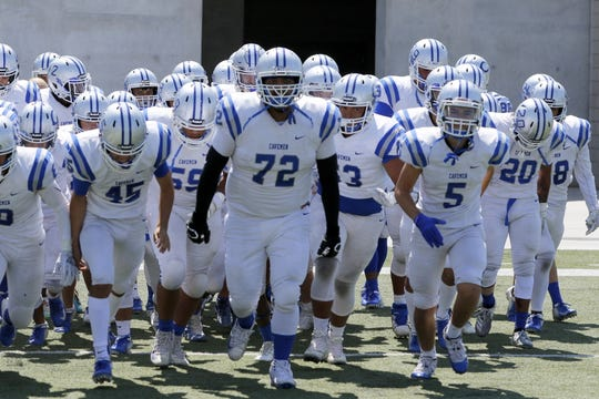 Darius Chavarria (72) leads the Carlsbad Cavemen onto the field against Atrisco Heritage on Sept. 8, 2019.