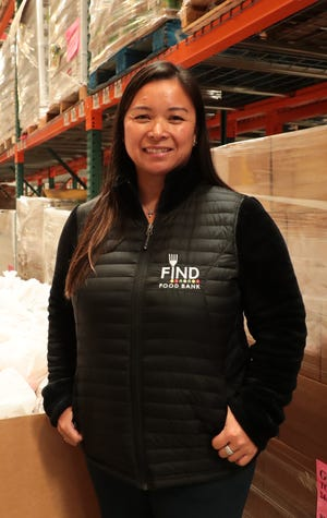 FIND Food Bank CEO Debbie Espinosa poses in front of bags of food in Indio, Calif., that will be distributed to help those affected by the coronavirus outbreak on Monday, March 23, 2020.