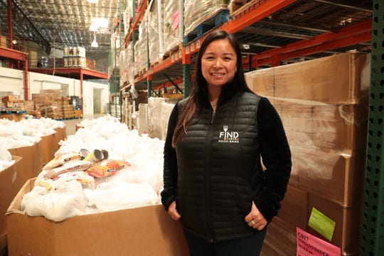 FIND Food Bank president Debbie Espinosa poses in front of bags of food in Indio, Calif. that will be distributed to help those affected by the coronavirus outbreak on Monday, March 23, 2020.