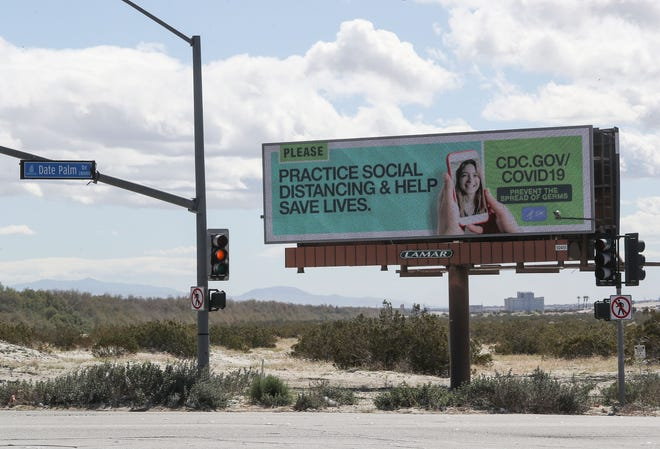 A billboard urges social distancing as the government steps up its coronavirus messaging in Cathedral City, March 23, 2020.