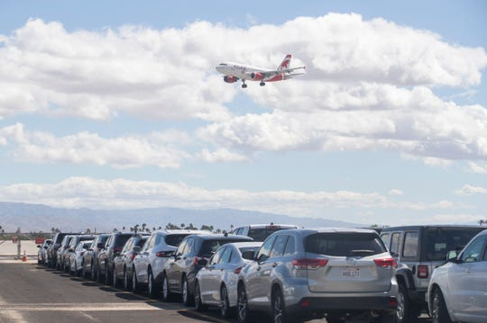 An airplane arrives at Palm Springs International Airport as rental cars are parked in a reservoir lot next to the landing strip on March 23, 2020. COVID-19 contingency has created a flood of unrented vehicles to sit flooding rental lots.