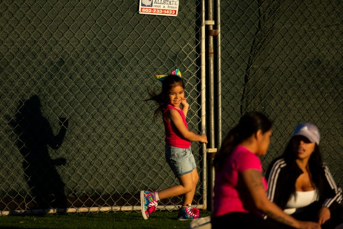 Five-year-old Emma Chavez enjoys an afternoon at Hance Park with her mother, Andrea Chavez (center) and family friend Michelle Lopez in Phoenix on March 21, 2020. Across the country government officials asked people to stay at home and