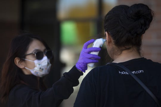 Medical assistant Rubi Salgado Guzman (left) checks a potential patient's temperature at the Mountain Park Health Center Maryvale Clinic in Phoenix on March 23, 2020.