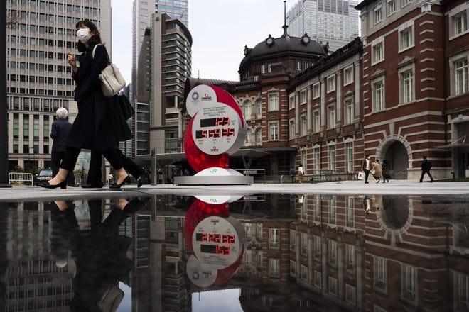 Un reloj de cuenta atrás se ve reflejado en un charco ante la estación de Tokio, en Tokio, el lunes 23 de marzo de 2020.