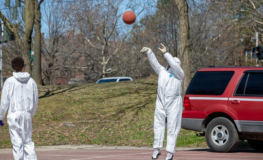 DJ Huggan fires a jump shot during a March 21 pickup basketball game in the City of Poughkeepsie. He and six friends played while wearing Hazmat suits.