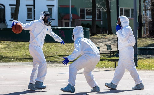Poughkeepsie, New York, native Tre Mayo sets up to crossover dribble during a pickup basketball game on Saturday, March 21, 2020. He and a group of friends played in hazmat suits amid the coronavirus scare.
