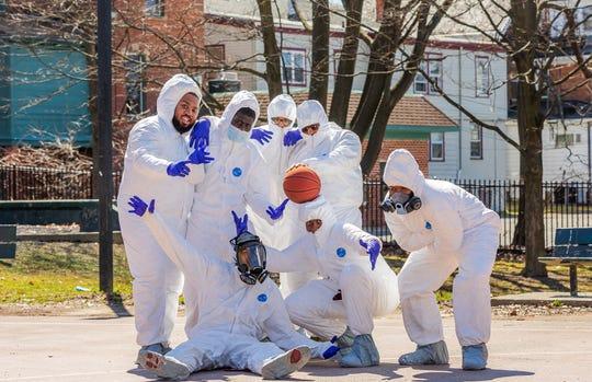 Friends Joshua Grant, Juane Mayo, DJ Huggan, Chris Mayo, Akeim Clarke, Jayvon Robinson and Tre Mayo pose for a photo after playing pickup basketball in Hazmat suits on Saturday.