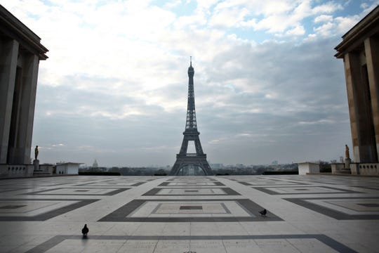 Pigeons walk on the Trocadero square in front of the Eiffel Tower, in Paris, March 18, 2020. (AP Photo/Thibault Camus)