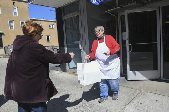 Mildred A. Kennedy, owner, of Momma Millie's Bakery, hands Christine Romanko, of Saint Clair, Pa., her blueberry pie, Jewish apple cake and sticky buns order in front of her bakery at 216 N. Centre Street in downtown Pottsville, Pa., on Saturday, March 21, 2020. She is taking orders on the phone or customers may stop at the store and call for her to come out. A sign is posted on her front door with her phone number. On Thursday, Gov. Tom Wolf ordered all non-life-sustaining businesses to close their physical locations as the COVID-19 pandemic worsens. Momma Millie's is staying open with curbside pickup only. (Jacqueline Dormer/The Republican-Herald via AP)