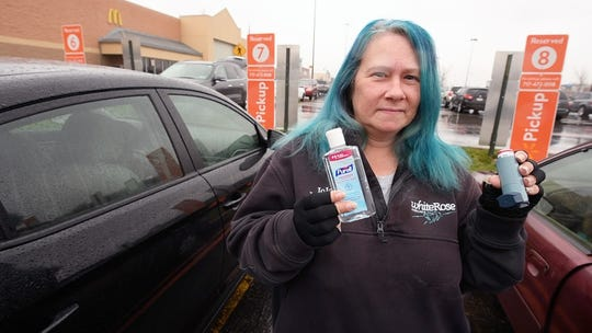 """Jolene Hunt holds up a bottle of hand sanitizer to protect her from the coronavirus and the inhaler she uses when her asthma flairs up saying, 'These are my weapons. This is what keeps me going in my job."""" Hunt delivers groceries for Walmart. Facing an eviction, Hunt is grateful to still have a job with the coronavirus outbreak closings; other members of her family aren't working."""