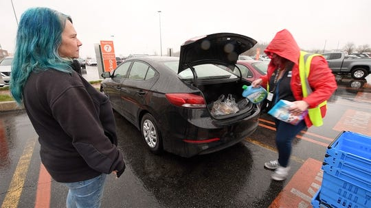 Jolene Hunt, left, watches groceries packed into her trunk at Walmart in West Manchester Township. Since the coronavirus, drivers aren't allowed to help grocery packers and all signatures are done without touching shared equipment.