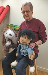 Bob Miller holds the puppets Hashim and Abner in his studio at MarketView Arts.