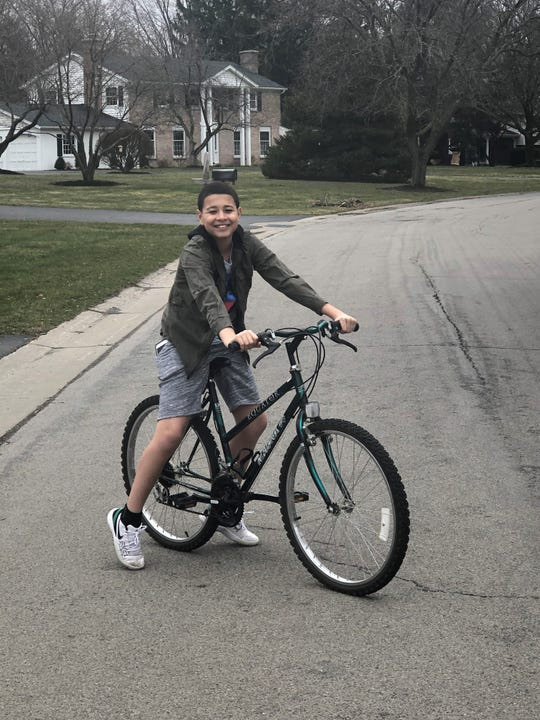 """Delwin Robinson, 12, rides his bike for """"gym class"""" outside his Pittsford home."""