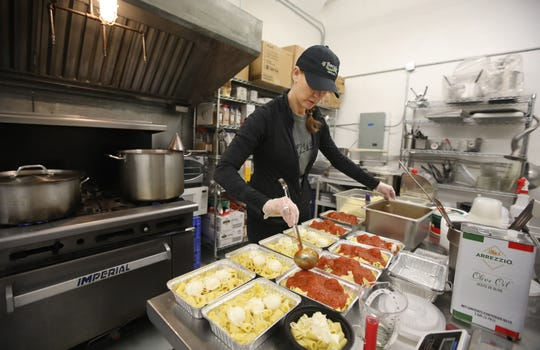 Marisa Bozza makes rigatoni bakes to fill delivery orders at her Bozza Pasta shop in Hilton Monday, March 23, 2020. Due to the coronavirus pandemic closing restaurants across the state, the Bozza family decided to start a delivery service out of his Hilton shop to help get his products to customers, and to help stay in business.