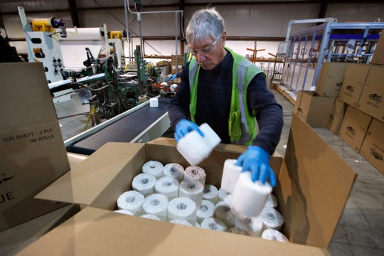 Scott Mitchell fills a box with toilet paper at the Tissue Plus factory, Wednesday, March 18, 2020, in Bangor, Maine.