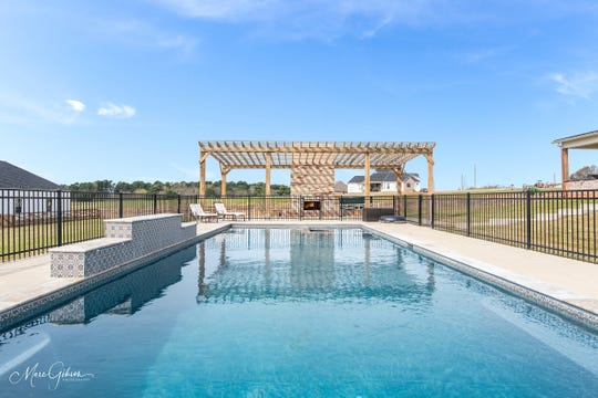 Dine al fresco under the oversized pergola overlooking the blue waters of the heated swimming pool.