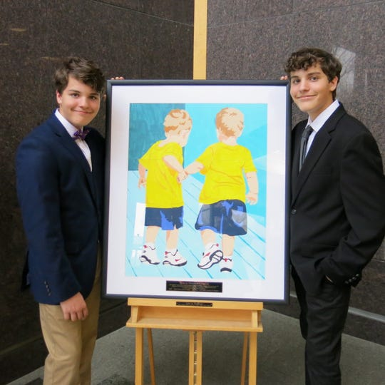 Twins Logan and Marshall O'Callaghan stand by a painting of themselves as toddlers. The photo was by their grandmother, the late Frances O' Callaghan, and inspired the invitation to a celebration for her.