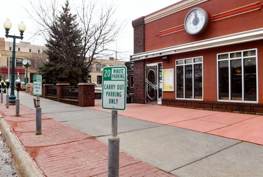 Signs designating parking spaces for carry-out customers only stand on Monday, March 23, outside the Phillips Avenue Diner in Sioux Falls. Restaurants are offering to-go orders to encourage social distancing as coronavirus concerns grow.