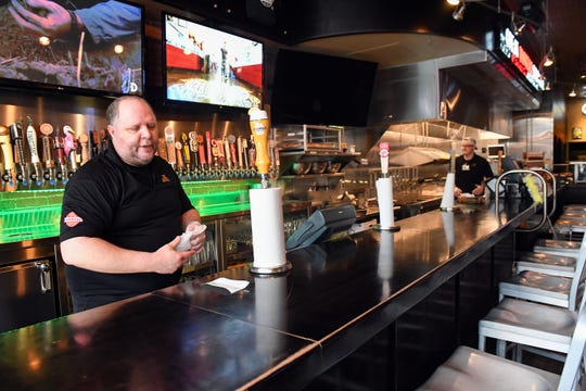 Troy Jacobsen and Kelby Beste prepare carry-out orders behind an empty bar on Monday, March 23, at JL Beers in Sioux Falls. Restaurants are offering to-go orders to encourage social distancing as coronavirus concerns grow.