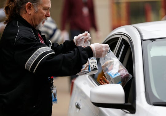 Springfield Public Schools employee Keith Durr hands a grab-and-go breakfast and lunch through an open car window to a family at Weaver Elementary on Monday, March 23, 2020. SPS is providing the free meals for students at 54 locations from 9:30 a.m. to 12:30 p.m. each weekday.