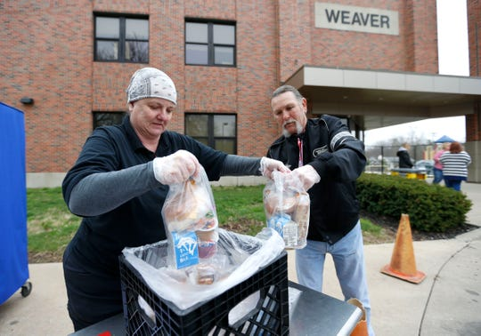 Springfield Public Schools employees Lynette Wright and Keith Durr pick up a grab-and-go breakfast and lunch to hand to a family at Weaver Elementary on Monday, March 23, 2020. SPS is providing the free meals for students at 54 locations from 9:30 a.m. to 12:30 p.m. each weekday.