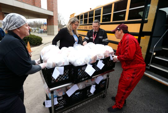 Springfield Public Schools employees load crates of grab-and-go breakfast and lunches into a school bus to take to other schools across the district at Weaver Elementary on Monday, March 23, 2020. SPS is providing the free meals for students at 54 locations from 9:30 a.m. to 12:30 p.m. each weekday.