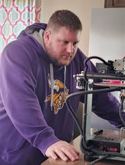 North Junior High teacher Rick Wilson uses a 3D printer to make a face mask Monday, March 23, at his Sartell home.