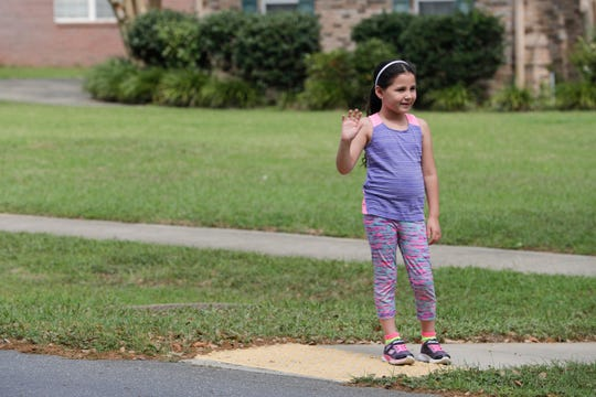 """Hawks Rise Elementary School families lined Meadow Ridge Drive in Ox Bottom neighborhood for a """"parade of smiles"""" that allowed the students to see their teachers while school has been closed until April 15 due to the coronavirus pandemic Monday, March 23, 2020."""