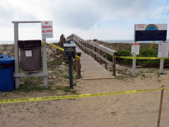 Police tape blocks access to St. George Island's popular beaches.