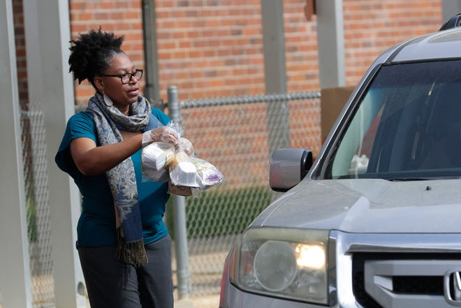 Volunteers hand food through car windows at W.T. Moore Elementary School as Leon County Schools provides food for families Monday, March 23, 2020.