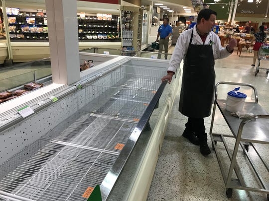 Grocery store employees clean and disinfect empty freezer cases while waiting for the next delivery.