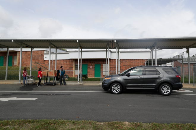 Cars line up along the bus pick-up area at W.T. Moore Elementary School as Leon County Schools provides food for students' families at 14 locations Monday, March 23, 2020.