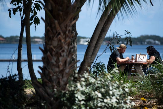 Brenden Yarbrough (left) and Brittany Nahrstedt, both of Port St. Lucie, enjoy their carry out order from Stuart Coffee Co. at a table along the St. Lucie River on Monday, March 23, 2020, in downtown Stuart. The couple had cabin fever and wanted to get outside, Yarbrough said.