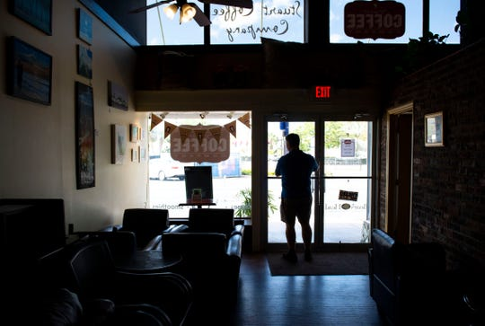 """Business is certainly off,"" said Foster Boop, owner of Stuart Coffee Co., who adjusted a sign on the door stating the shop is open with carry-out service Monday, March 23, 2020, in downtown Stuart. Boop has had to lay off and furlough employees as the coronavirus pandemic grows, but is encouraged to see some regulars and others in the community coming in for coffee and breakfast. ""The biggest challenge is the unknown, not knowing how long it will last,"" he said."