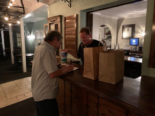 Mike Gabriel, left, signs for his takeout order Friday night March 20, 2020, at The Tides restaurant in Vero Beach. Florida rules passed during the COVID-19 crisis limit restaurants to takeout or delivery only. The Tides' Kevin Fitzpatrick handled checkout duties.