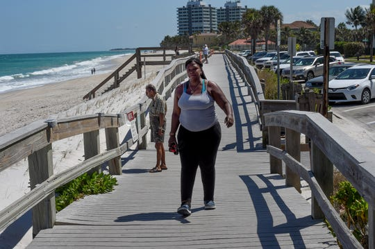 Terra Carroll of Vero Beach walks the boardwalk along Conn Beach and Jaycee Park in Vero Beach on Monday, March 23, 2020. The boardwalk is open, but people cannot go onto the closed beach.