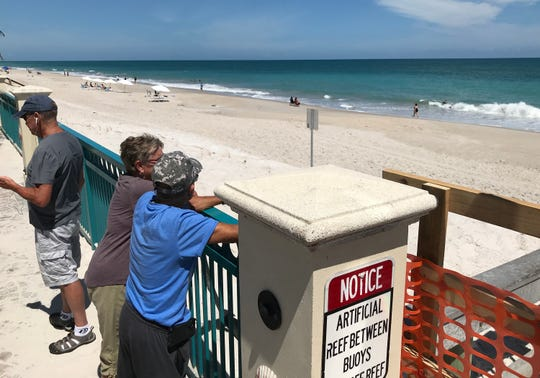 """Danny Young (from right), his wife Mary Beth, winter residents from Massachusetts, along with Danny's brother, Dave Young, from Colorado, overlook the beach Monday, March 23, 2020, where hotel guests are relaxing near Sexton Plaza in Vero Beach. Public access to the beach is closed. """"It's sad that I can't be there with them. I guess I got to get a room at the hotel to go to the beach,"""" Danny Young said."""