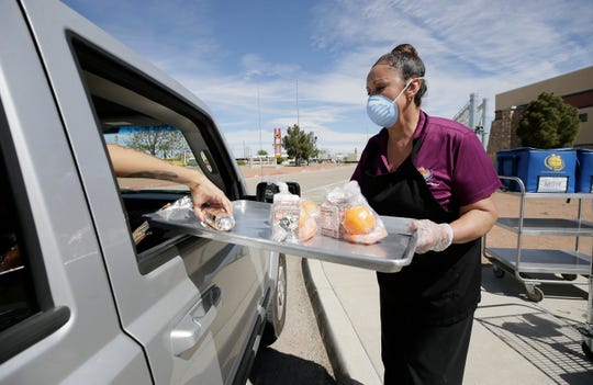 Licha Escalera of Moye Elementary School helps children and parents get free meals from a tray Monday, March 23, 2020, outside the school.