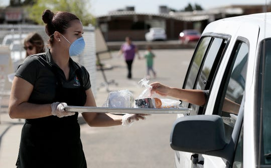 Nancy Nuñez, a cafeteria worker at Moye Elementary School, serves curbside meals to children Monday, March 23, 2020, outside the Northeast El Paso school. The EPISD will continue to provide breakfast and lunch free of charge at several locations.