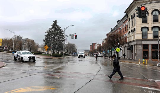 A few pedestrians and two police cars were seen in an otherwise deserted Ossining, N.Y. March 23, 2020. Coronavirus related restrictions have closed most businesses and kept people indoors.