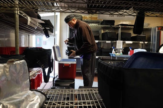 Brian Shaw, a kitchen manager at St. Anthony's Community Center, fills coolers with food to be delivered by Meals on Wheels volunteers to senior in need of food assistance.